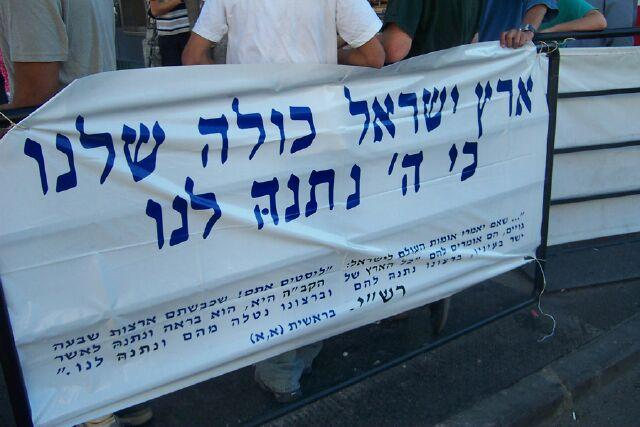 Demonstrators holding a sign in Hebrew reading 'All the land of Israel is ours, because God gave it to us.' (Photo: Jacob Richman)