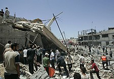 Palestinians gather by a building destroyed in an explosion in the town of Beit Lahiya, northern Gaza. (AP)
