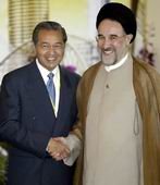 Malaysian PM Mahathir Mohamad (L) greeting Iran's Mohammad Khatami at the OIC summit in Putrajaya on Thursday.