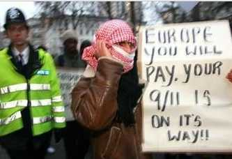 Muslim demonstrator with sign: 'EUROPE YOU WILL PAY.  YOUR 9/11 IS ON ITS WAY!!'