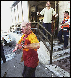 Wounded Israelis leave the scene of today's suicide bombing.