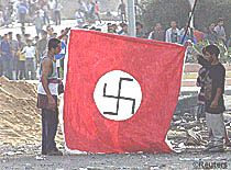 October 6, 2000: Palestinians hold up flag with a Nazi swastika in front of an Israeli army outpost at the Netzarim junction, Gaza Strip, in support of the Nazi goal of genocide against the Jewish people.