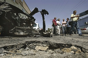 People gather at the site where a rocket fired by Palestinians from Gaza killed a woman in Sderot. (AP)